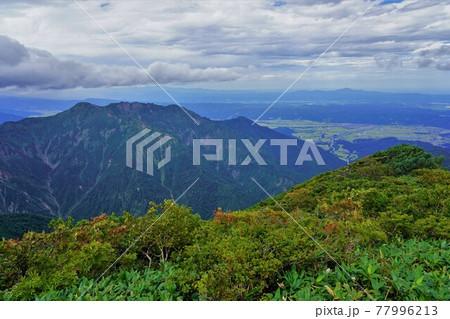 越後駒ヶ岳山頂からの八海山と街並み 77996213
