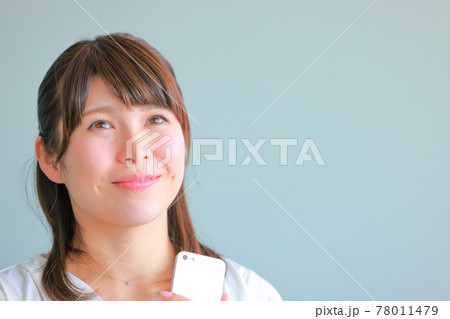 スマホを持ちにこやかに空想する女性 78011479