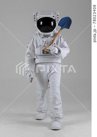 Walking astronaut carrying farm tools, shovel, white background 78023408