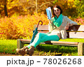 Woman reading book sitting on bench in park 78026268