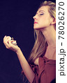 Beautiful woman with holding and applying perfume 78026270