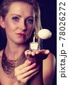 Beautiful woman with necklace holding perfume 78026272