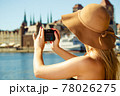 Beautiful elegant woman taking pictures with camera 78026275