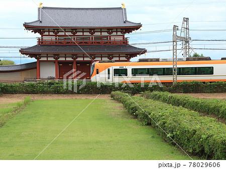 奈良市西部に広がる世界遺産の平城宮跡に復元された朱雀門の前を通過する近鉄奈良線の特急列車 78029606