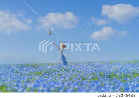 ネモフィラの丘で帽子を投げる女の子 78076438