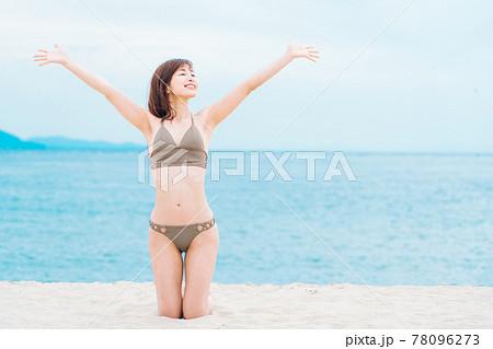 砂浜で膝立ちする水着の女性 78096273