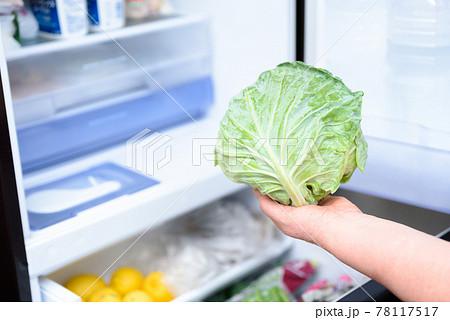 料理のために冷蔵庫からキャベツを取り出す女性の手 扉を開けた冷蔵庫 78117517