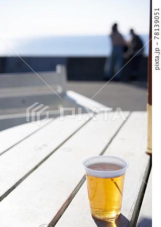 青い海が見えるテラス席のテーブルに置かれたビールのグラス 78139051
