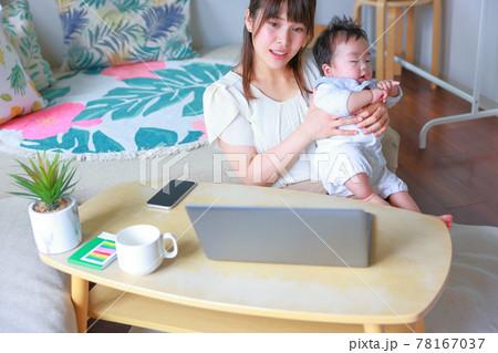 乳児をだっこして微笑むテレワークの母親 78167037
