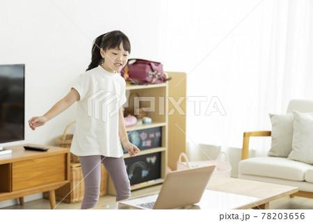 パソコンを見ながらダンスをする女の子 78203656