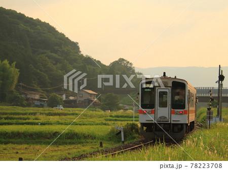 JR名松線で民家の前に広がる田んぼの中を走行するディーゼルカー 78223708