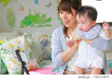 ビデオ通話_手を挙げる乳児と笑顔の母親 78225845