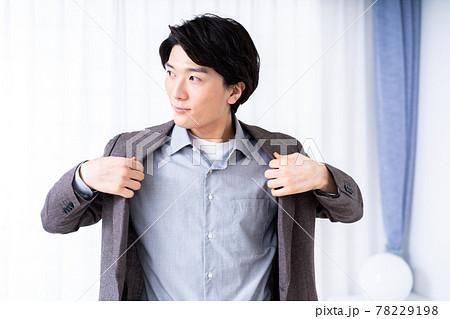 リビングでスーツの上着を着る男性 78229198