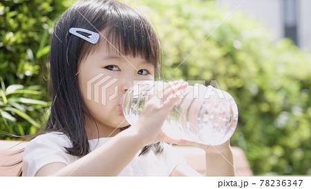 外のベンチに座って水分補給をする子供 78236347