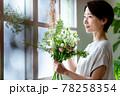 窓際で花束を見る女性 78258354