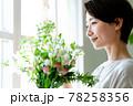 窓際で花束を見る女性 78258356
