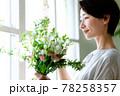 窓際で花束を見る女性 78258357