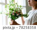窓際で花束を見る女性 78258358