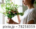 窓際で花束を見る女性 78258359