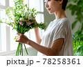 窓際で花束を見る女性 78258361