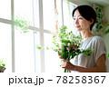 窓際で花束を見る女性 78258367
