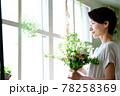 窓際で花束を見る女性 78258369