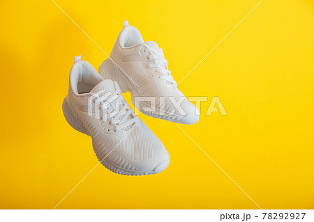 Levitation white sport shoes footwear on yellow wall. White sneakers shoes fly on yellow color background with copy space. Pair of sport male sneakers. 78292927