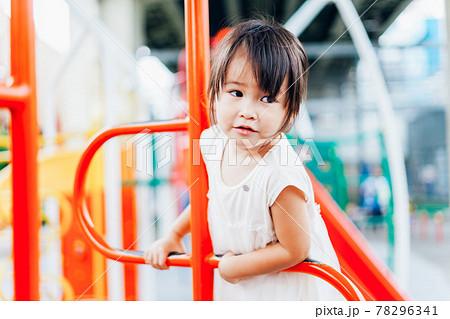 公園の遊具で遊ぶ小さな女の子 78296341