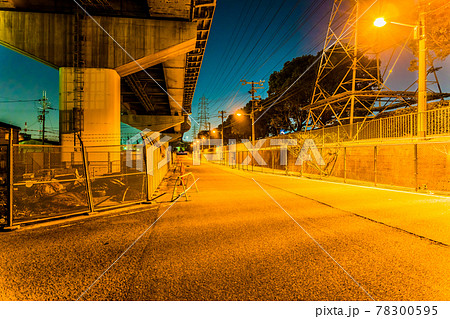高速道路の下で街灯に照らされる道路 78300595