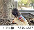 木の前でプリンセスの服を来た女の子が座っている 78301887