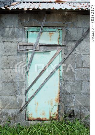 ブロック塀とグリーンの扉に無造作に打ち付けられた板 78332177