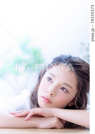 テーブルに伏せる若い女性の顔のアップ 78350373