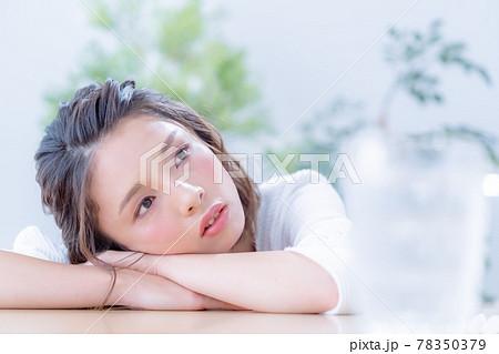 テーブルに伏せる若い女性の顔のアップ 78350379
