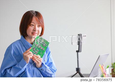 スマホでオンラインミーティング_基板を持ちにこやかに話す作業着の女性 78356975