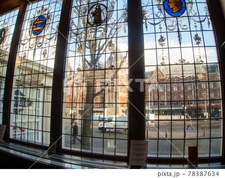 ガラス窓越しに見えるオランダアムステルダムの赤煉瓦造りの中央駅 78387634