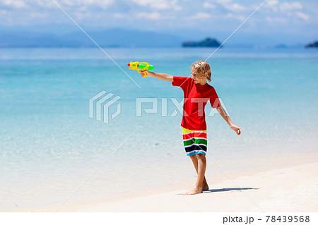Child with toy water gun. Kids vacation beach fun. 78439568