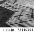 タイル張りの歩道と歩道橋の階段の手摺の影、白黒 78440354