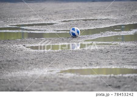 雨あがりのグラウンドに置かれたサッカーボール 78453242