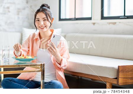 リビングでパスタを食べながらスマホを見る若い女性 78454348
