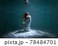 Woman in a dress is dancing underwater. 78484701