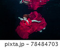 Woman in a red dress swims underwater. 78484703
