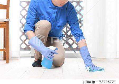 部屋で床掃除をする清掃業の作業服の若い男性 78498221