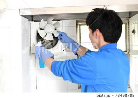 換気扇の掃除をする清掃業の作業服の若い男性 78498788