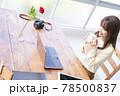窓辺でパソコンの前の席に座りコーヒーを飲む20代女性 78500837