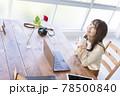 窓辺でパソコンの前の席に座りコーヒーを飲む20代女性 78500840