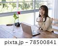 窓辺でパソコンの前の席に座りコーヒーを飲む20代女性 78500841