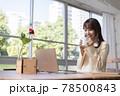 窓際でパソコンの前の席に座りコーヒーを飲む20代女性 78500843