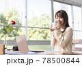 窓辺でパソコンの前の席に座りコーヒーを飲む20代女性 78500844