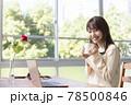 窓辺でパソコンの前の席に座りコーヒーを飲む20代女性 78500846