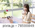窓辺でパソコンの前の席に座りコーヒーを飲む20代女性 78500849